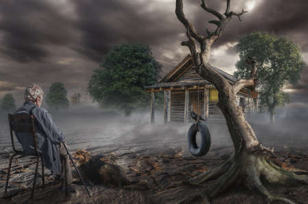 solitary: an elderly gray-haired man sits near a dry tree on the spot where was the house of his childhood