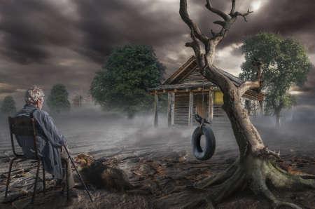 un hombre de cabello gris hombre se sienta cerca de un árbol seco en el lugar donde estaba la casa de su infancia