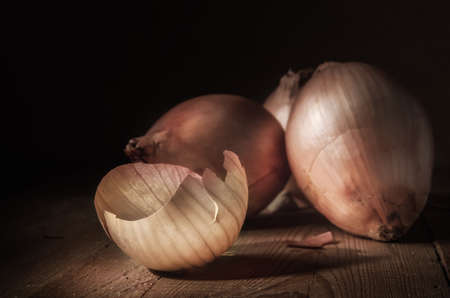 onions and peel on a dark wooden background