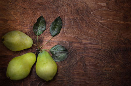 group and three pears in a rustic style on a dark wooden background