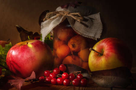 apples and branches of viburnum on a dark wooden background in a rustic style.
