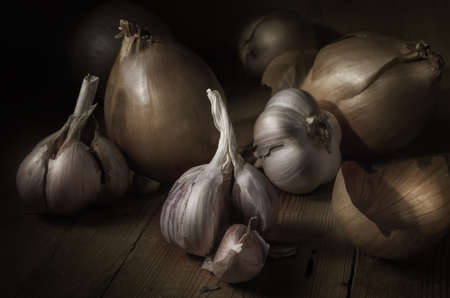 onions and garlic on a dark wooden background