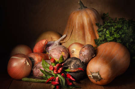 pumpkin and other vegetables in a rustic style on a dark wooden background