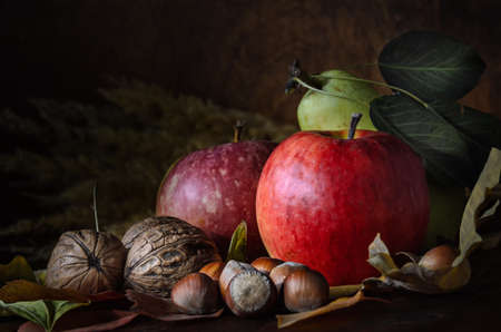 nuts and fruits with foliage in rustic style on dark wooden background