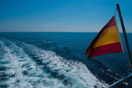 View form the back of the yacht - spanish flag and the waves under solid blue sky photo