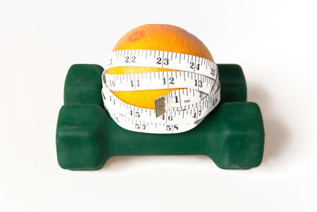 inches: Grapefruit with measure tape in inches on dumbbells