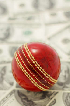 Red cricket ball and money Stock Photo