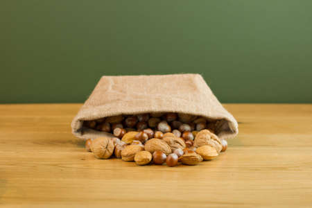 Hessian sack with mixed nuts spilling out Stock Photo