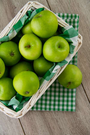 Green apples in white basket Stock Photo