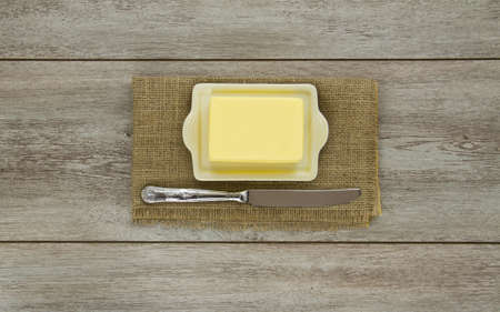 Fresh block of creamy yellow butter, on a cream ceramic butter dish laid on burlap with a silver engraved butter knife lying beside. On weathered boards. Stock Photo