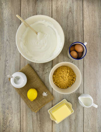 Raw ingredients to make a classic new york baked cheesecake with lemon, on burlap and weathered boards.