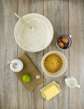 Raw ingredients to make a classic new york baked cheesecake with lime, on burlap and weathered boards.