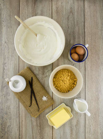Raw ingredients to make a classic new york baked cheesecake with vanilla on burlap and weathered boards. Stock Photo