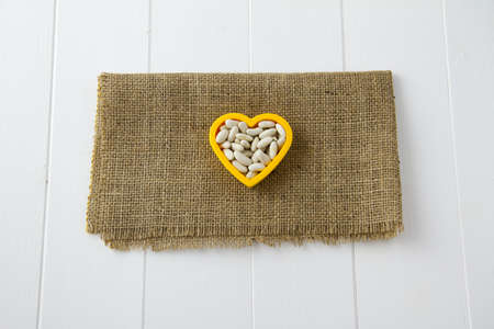 Raw cannellini beans nestled in a heart, sitting on burlap and white wooden boards Stock Photo