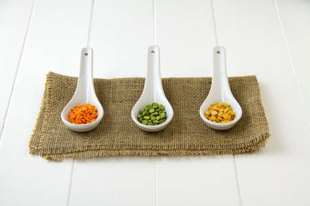 Raw, dried red lentils, green lentils and yellow lentils in three white ceramic spoons, sitting on burlap and white wooden boards