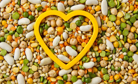 Mixed grains, pulses, beans, peas and legumes, filling the frame with yellow heart photo