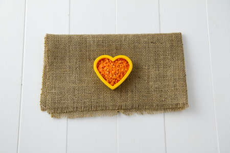 Raw red lentils nestled in a heart, sitting on burlap and white wooden boards