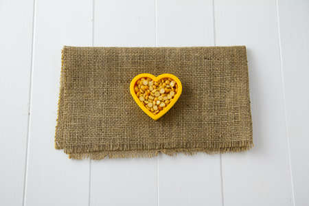 Raw yellow lentils nestled in a heart, sitting on burlap and white wooden boards photo