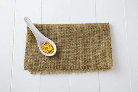 Raw yellow lentils in a white ceramic spoon, sitting on burlap and white wooden boards