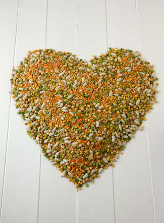 Mixed grains, pulses, beans, peas and legumes, shaped into a heart on white painted wood