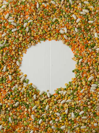 Mixed grains, pulses, beans, peas and legumes, with copy space on white painted wood Stock Photo