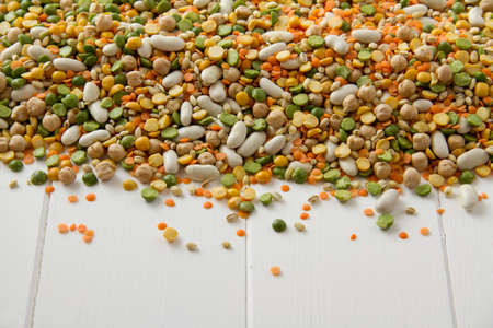 Mixed grains, pulses, beans, peas and legumes, spilling onto white painted wood