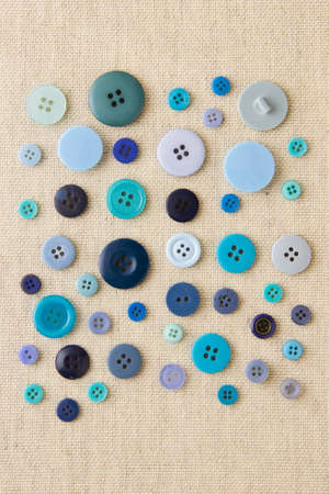 Many blue sewing or clothing buttons on hessian Stock Photo