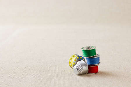 Sewing machine bobbins on hessian with thimble Stock Photo
