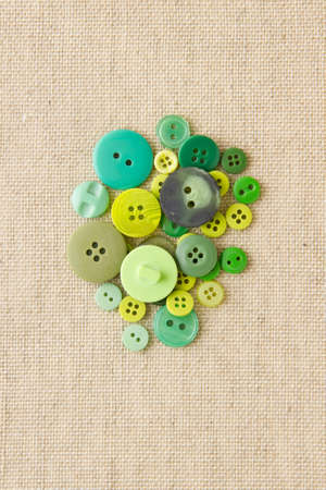 Many green sewing or clothing buttons on hessian