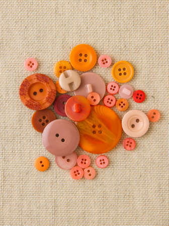Many orange sewing or clothing buttons on hessian