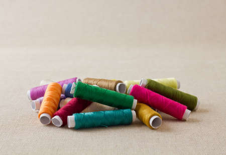 Pile of thread spools or bobbins, mixed colours Stock Photo