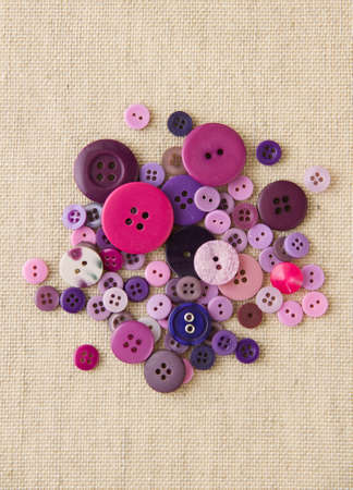 Many purple sewing or clothing buttons on hessian