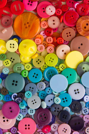 Mixed coloured bright buttons, arranged in rainbow colour formation, filling the frame Stock Photo