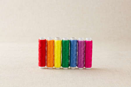 Spools or bobbins of thread, brightly coloured, arranged in rainbow colour formation