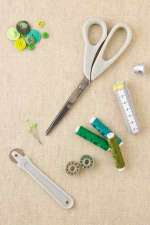 Various sewing items, including scissors, tailors wheel, bobbins, spools of thread, measuring tape, thimble and buttons in harmonising green tones Stock Photo