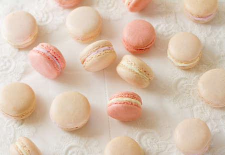 Assortment of French macarons (pronounced macaroon, a popular buttercream filled meringue type cookie or biscuit)  on white wood table with lace over, in soft pink and white hues. A fresh, feminine image.