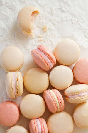 A pile of French macarons (pronounced macaroon, a popular buttercream filled meringue type cookie or biscuit) on white wood and lace. One macaron has had a bite taken out of it. A fresh, feminine image.