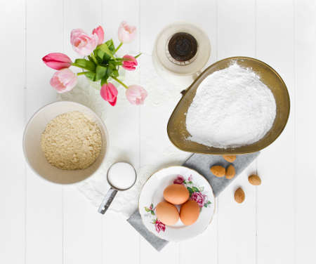 Ingredients for French macarons (pronounced macaroon, a popular buttercream filled meringue type cookie or biscuit) laid out, viewed from above on white wood, with lace and blue napkin. Ingredients include ground almonds (or almond flour), icing sugar (po Stock Photo