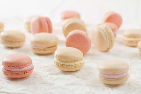 French macarons (pronounced macaroon, a popular buttercream filled meringue type cookie or biscuit) on white wood table with lace over. In soft pink and white hues with bright backlight. A fresh, feminine image.