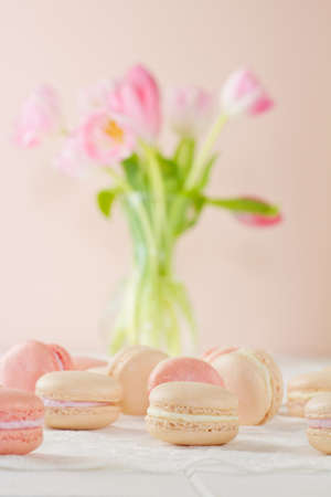 Assortment of French macarons (pronounced macaroon, a popular buttercream filled meringue type cookie or biscuit) on white wood table with lace over Soft pink and white tulips sit behind. A fresh, feminine image. Stock Photo