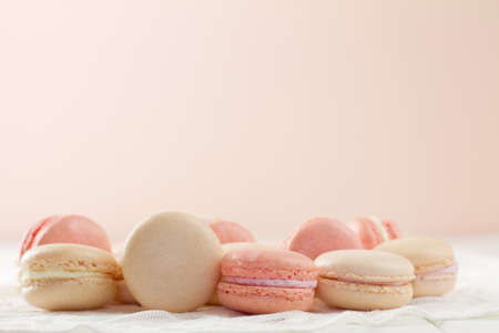 French macarons (pronounced macaroon, a popular buttercream filled meringue type cookie or biscuit) on white wood table with lace over Soft pink and white hues with copy space. A fresh, feminine image.