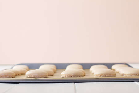 A tray of French macarons (pronounced macaroon, a popular buttercream filled meringue type cookie or biscuit) on a baking sheet lined with baking parchment paper, on white wood table. Soft pink background. A fresh, feminine image. Stock Photo