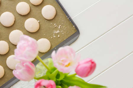 A tray of French macarons (pronounced macaroon, a popular buttercream filled meringue type cookie or biscuit) on a baking sheet lined with baking parchment paper, on white wood table. One has been eaten, only crumbs remain. Soft pink and white tulips sit