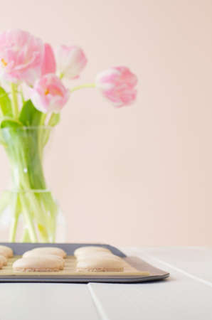 A tray of French macarons (pronounced macaroon, a popular buttercream filled meringue type cookie or biscuit) on a baking sheet lined with baking parchment paper, on white wood table. Soft pink background with fresh tulips in a vase. A bright, feminine im Stock Photo