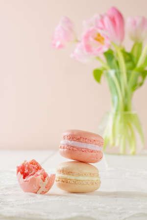 Three French macarons (pronounced macaroon, a popular buttercream filled meringue type cookie or biscuit) in stacked formation, on white wood table with lace placemat. One has had a bite taken out of it. Soft pink and white tulips sit in a vase in the bac