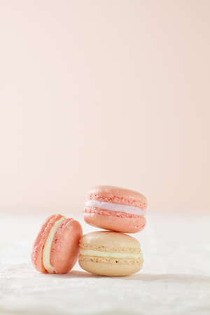 Three French macaron (pronounced macaroon, a popular buttercream filled meringue type cookie or biscuit) in a stacked formation, on white wood table with lace placemat on a soft pink background. Stock Photo