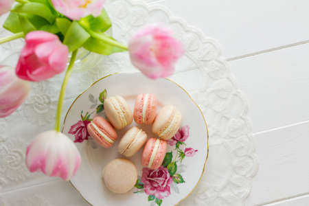 Seven French macarons (pronounced macaroon, a popular buttercream filled meringue type cookie or biscuit) on a dainty porcelain, rose patterned and gilded plate, on white wood table with lace placemat. Soft pink and white tulips sit to one side. A fresh,