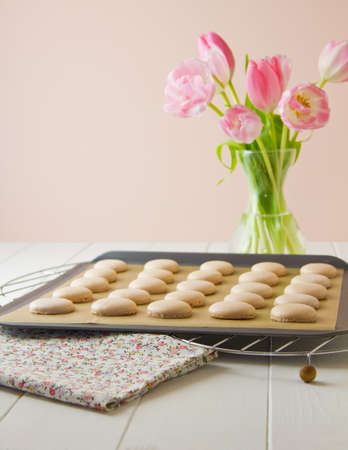 25 French macaron shells (pronounced macaroon, a popular buttercream filled meringue type cookie or biscuit) on baking sheet lined with baking parchment paper, on wire cooling racks. On white wood table with floral tea towel. Soft pink and white tulips si