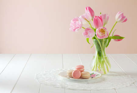 A heap of French macarons (pronounced macaroon, a popular buttercream filled meringue type cookie or biscuit) on a dainty porcelain, rose patterned and gilded plate, on white wood table with lace placemat. Soft pink and white tulips sit to one side. A fre