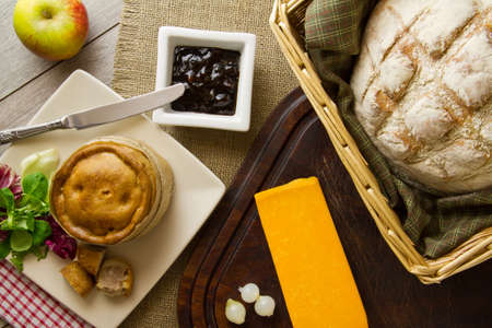 A typical ploughmans lunch fare, spread out on burlap, bread board and distressed boards. Melton Mowbray pork pie with artisan boule bread in basket, next to red Leicester cheese, butter, salad and an apple. Stock Photo